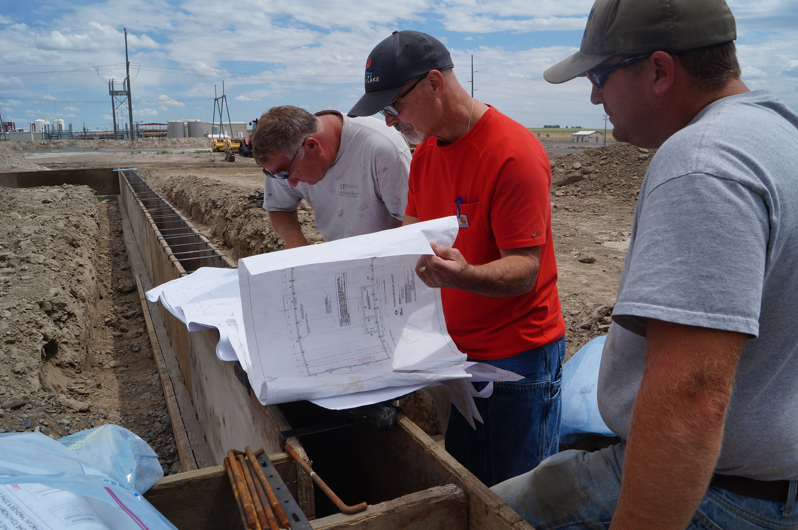 Building Inspector Robert Trumbull, center in red shirt, discusses plans at the Cascade Agronomics s