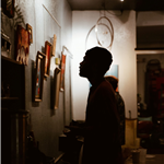 a silhouette of a man looking at art hanging from the wall