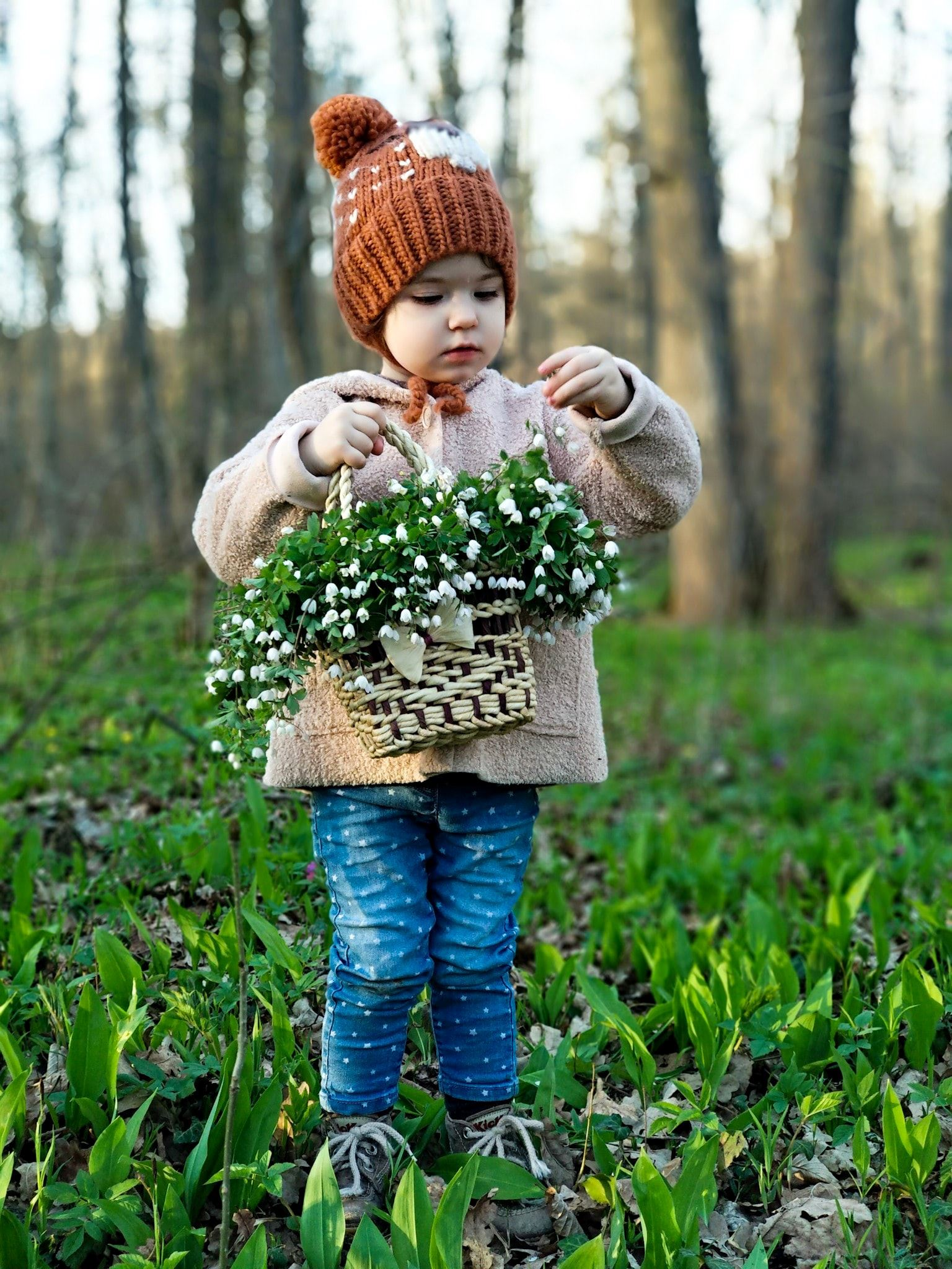 young girl in green field holding a basket of flowers