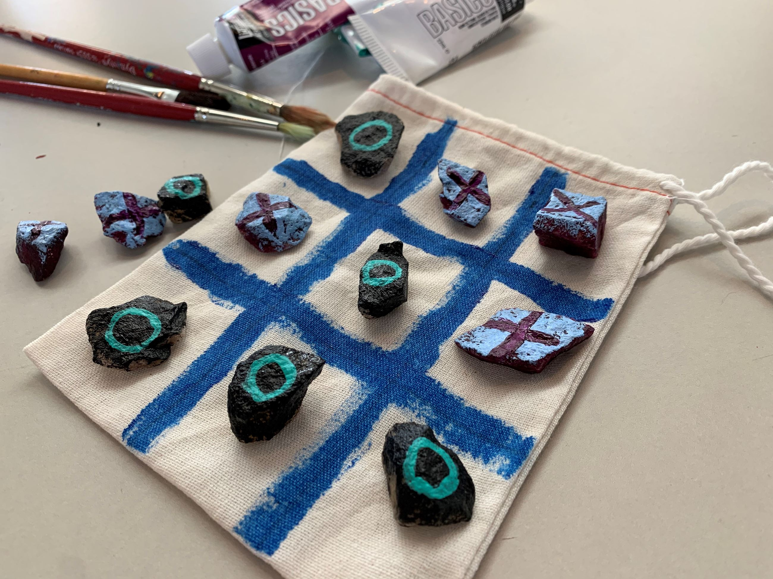 cloth bag with painted stones to make a tic tac toe game