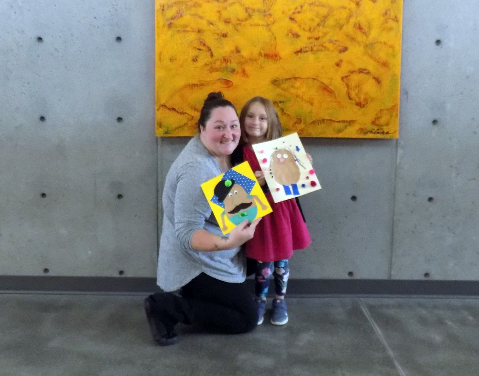 Woman and child showing off art work